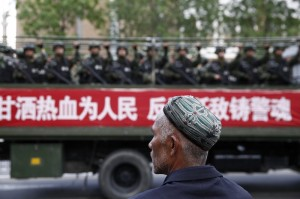 A Uighur man looks on as a truck carrying paramilitary policemen travel along a street during an anti-terrorism oath-taking rally in Urumqi