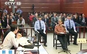 Uighur academic Ilham Tohti sits in a chair at the stand during his trial on separatism charges in Urumqi, Xinjiang region