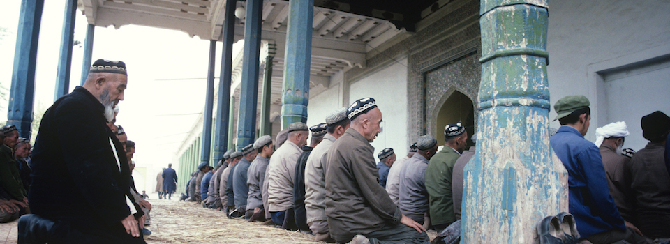 China, Xinjiang Province, Kashgar, men praying at mosque, sunset