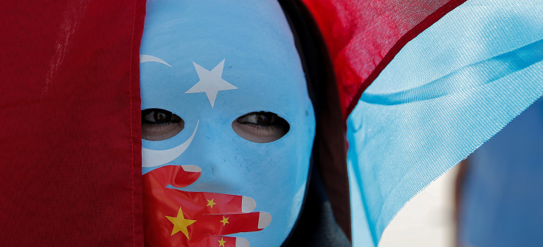 An ethnic Uighur demonstrator wears a mask as she attends a protest against China in front of the Chinese Consulate in Istanbul